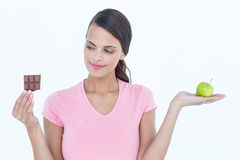 Pretty woman holding chocolate bars and an apple Stock Photography