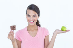 Pretty woman holding chocolate bars and an apple Royalty Free Stock Photos