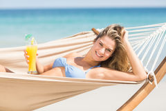 Pretty woman holding cocktail in the hammock Royalty Free Stock Images