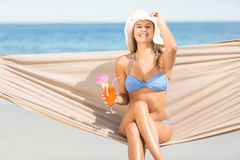 Pretty woman holding cocktail in the hammock Royalty Free Stock Image