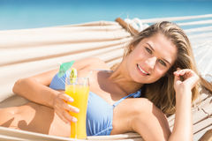 Pretty woman holding cocktail in the hammock Stock Photos