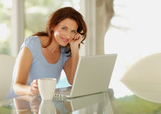 Pretty woman holding coffee cup in front of laptop Royalty Free Stock Images