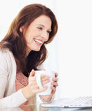 Pretty woman holding coffee cup by laptop Stock Images