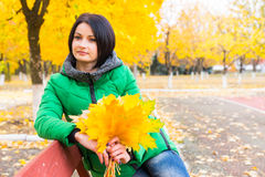 Pretty woman holding colorful yellow fall leaves Stock Photography