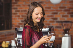 Pretty woman holding a cup of coffee and texting Royalty Free Stock Image