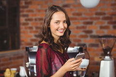 Pretty woman holding a cup of coffee and texting Royalty Free Stock Photos
