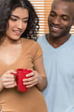 Pretty woman holding cup and man looking at her. Royalty Free Stock Photography