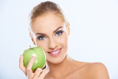 Pretty woman holding a fresh green apple. Pretty young blond woman with a friendly smile holding a fresh juicy green green apple in a healthy diet and wellness Stock Photography