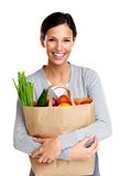 Pretty woman holding a grocery bag and smiling Royalty Free Stock Photos