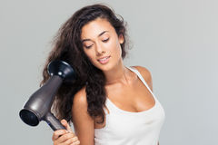 Pretty woman holding hairdryer Stock Photos