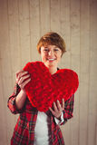 Pretty woman holding a heart pillow. On wooden planks background Stock Images