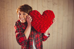 Pretty woman holding a heart pillow. On wooden planks background Royalty Free Stock Photography