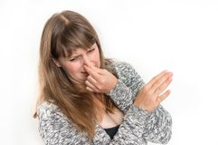 Woman is holding her nose - bad smell concept. Pretty woman is holding her nose - bad smell concept royalty free stock image