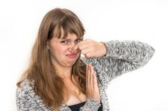 Woman is holding her nose - bad smell concept. Pretty woman is holding her nose - bad smell concept royalty free stock photo