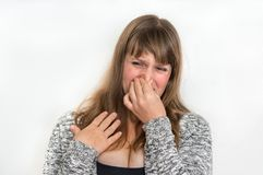 Woman is holding her nose - bad smell concept. Pretty woman is holding her nose - bad smell concept royalty free stock photos