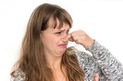 Woman is holding her nose - bad smell concept. Pretty woman is holding her nose - bad smell concept stock photos