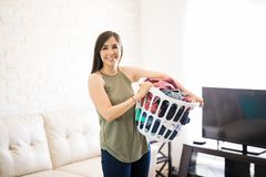 Pretty woman holding laundry basket. Portrait of a young hispanic woman holding a basket full of clothes Royalty Free Stock Images