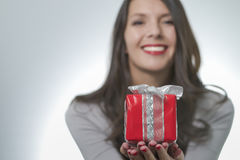Pretty woman holding out a gift Stock Photos