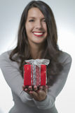 Pretty woman holding out a gift Stock Photo