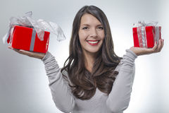 Pretty woman holding out two gifts Stock Photo