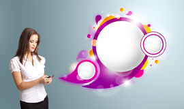 Pretty woman holding a phone and presenting abstract speech bubb Royalty Free Stock Images