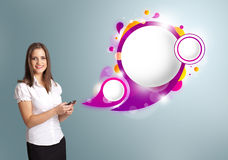 Pretty woman holding a phone and presenting abstract speech bubb Stock Photos