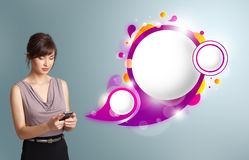 Pretty woman holding a phone and presenting abstract speech bubb. Pretty young woman holding a phone and presenting abstract speech bubble copy space Stock Photo