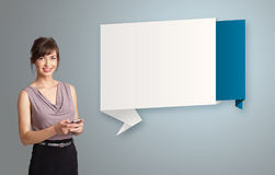 Pretty woman holding a phone and presenting modern origami copy Royalty Free Stock Image