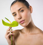 Pretty woman holding a plant leaf. Portrait of a beautiful naked and relaxed woman holding a plant leaf. Beauty and wellness concept Stock Photo