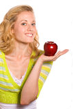 Pretty Woman Holding Red Apple. Attractive Blond Lady Holding a Juicy Red and Delicious Apple Stock Photo