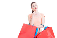 Pretty woman holding shopping bags feeling pensive or thoughtful Royalty Free Stock Photography