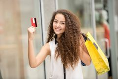 Pretty woman holding shopping bags and showing Stock Photos