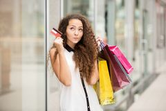 Pretty woman holding shopping bags and showing Stock Image