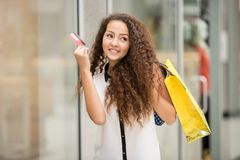 Pretty woman holding shopping bags and showing Royalty Free Stock Photos