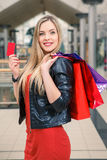 Pretty woman holding shopping bags and showing Royalty Free Stock Photo
