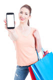 Pretty woman holding shopping bags showing blank mobile concept Royalty Free Stock Photos