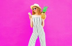 pretty woman holding smartphone, pineapple in summer round hat, white striped jumsuit on colorful pink wall royalty free stock image