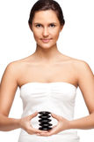Pretty woman holding stones for spa. Pretty woman portrait who holding stones for spa over white Stock Photography