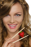 Pretty woman holding strawberry with chopsticks Stock Image