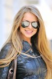 Pretty woman holding sunglasses. Pretty woman in sunglasses smiling outdoors stock photo