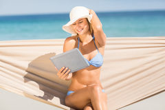 Pretty woman holding tablet pc in the hammock Royalty Free Stock Photos