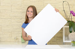 Pretty woman holding up a blank white sign. In front of her chest as she gives the camera a lovely smile - copyspace for your text or advertising Royalty Free Stock Photos