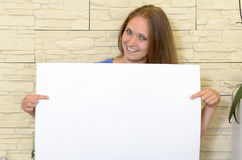 Pretty woman holding up a blank white sign. In front of her chest as she gives the camera a lovely smile - copyspace for your text or advertising Royalty Free Stock Photography