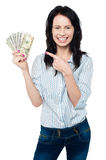 Pretty woman holding up fan of dollar notes Royalty Free Stock Photo