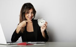 Pretty woman holding white vintage alarm clock and showing hand OK symbol over empty gray color background. Pretty woman holding white vintage alarm clock and stock photo