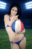 Pretty woman holds a ball at the field Stock Photos