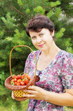 Pretty woman holds a basket with red strawberry Stock Photos