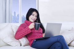 Pretty woman holds hot coffee and laptop Stock Photo