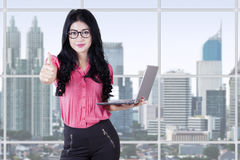 Pretty woman holds laptop and shows thumb up Royalty Free Stock Photography