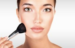 Pretty woman holds makeup brush against a grey background royalty free stock image